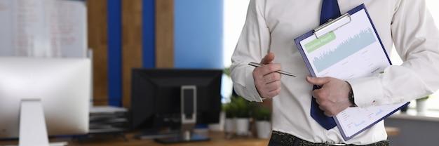 Empresário masculino segure a área de transferência com gráfico de negócios na mão