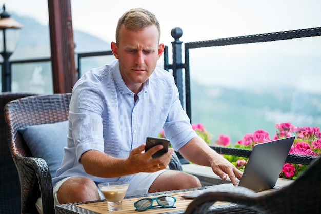 Empresário masculino trabalhando em um laptop de férias com uma bela vista panorâmica. gerente de sucesso tomando café e falando ao telefone com café enquanto viaja