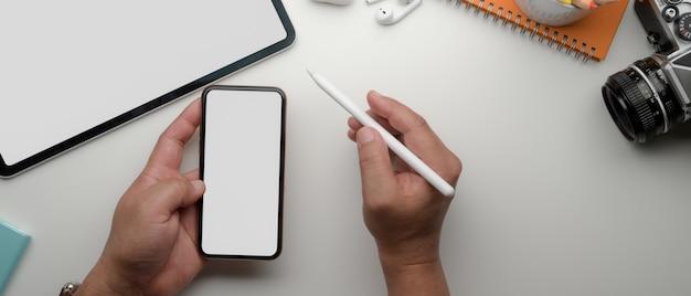 Empresário masculino usando smartphone acima da mesa de escritório branca com laptop e suprimentos