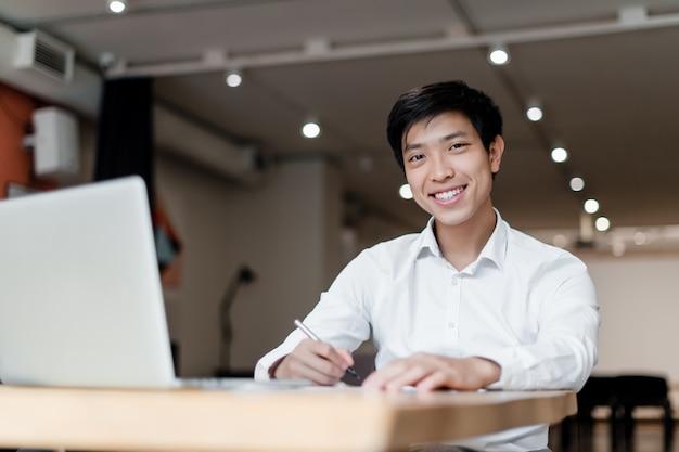 Empresário milenar asiático com laptop trabalha na mesa com documentos