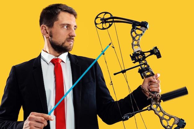 Empresário mirando no alvo com arco e flecha, isolado na parede amarela do estúdio