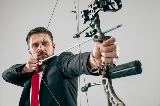 Empresário mirando no alvo com arco e flecha, isolado na parede cinza do estúdio