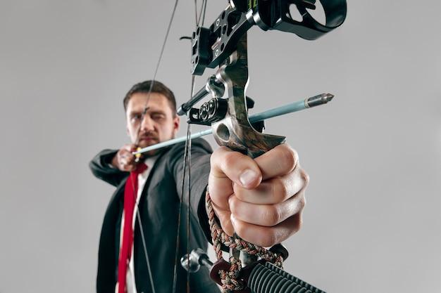 Empresário mirando no alvo com arco e flecha, isolado no fundo branco