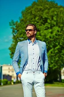 Empresário modelo homem de terno azul estilo de vida de pano na rua em óculos de sol
