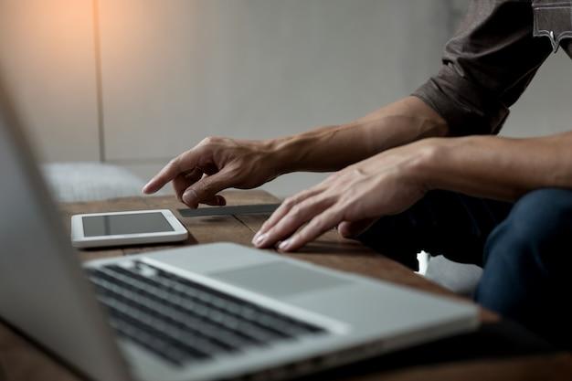 Empresário moderno com computador comprimido lendo notícias e documento de relatório de trabalho de manhã no café.