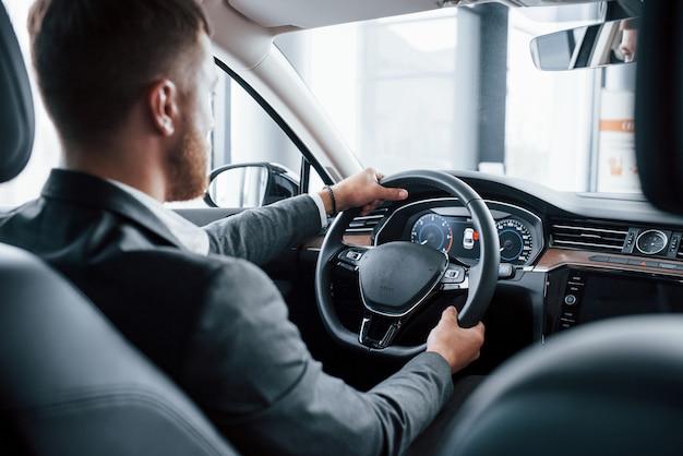 Empresário moderno experimentando seu novo carro no salão automotivo