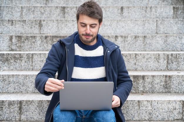 Empresário moderno hipster bonito, usando o laptop na cidade, com expressão positiva.