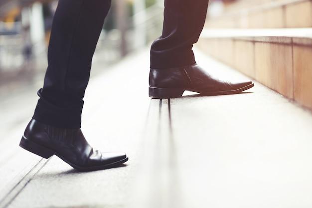 Empresário moderno, trabalhando as pernas de close-up, subindo as escadas na cidade moderna. na hora do rush para trabalhar no escritório com pressa. durante a primeira manhã de trabalho. escada. foco suave.