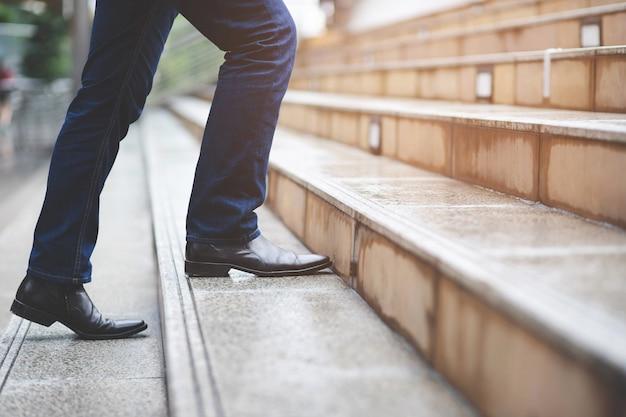 Empresário moderno, trabalhando as pernas de close-up, subindo as escadas na cidade moderna.