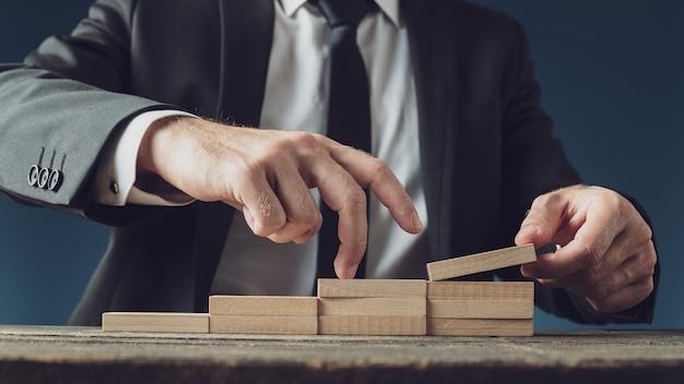 Empresário montando uma escada de pinos de madeira enquanto sobe os dedos em uma imagem conceitual.