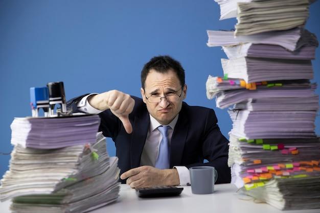Empresário mostra dedo sentado na mesa do escritório com uma enorme pilha de documentos, parecendo triste e deprimido