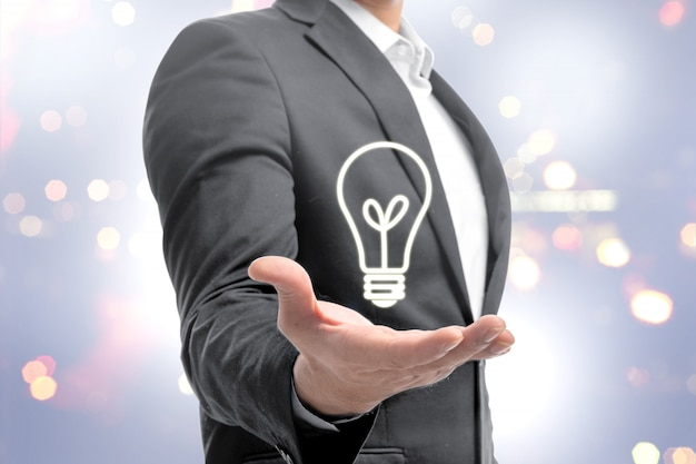 Empresário, mostrando a lâmpada brilhante nas mãos como um símbolo da ideia inovadora