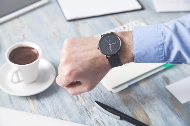 Empresário, mostrando o relógio de pulso na mesa do escritório.