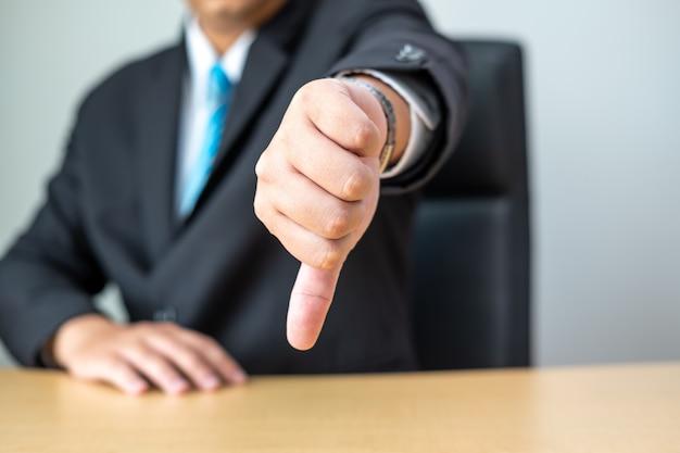 Empresário, mostrando os polegares para baixo na mesa