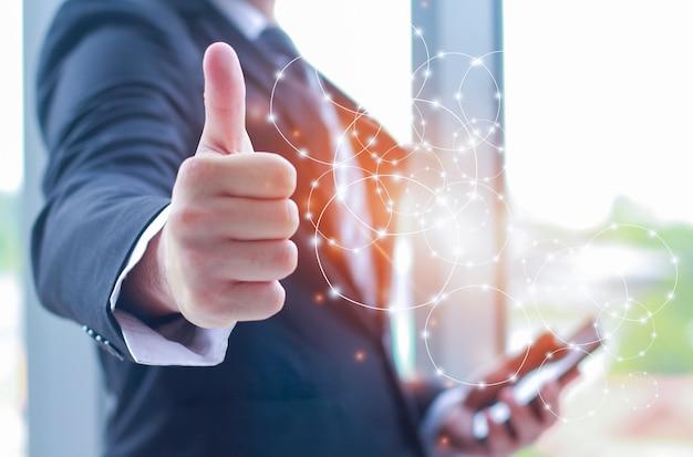 Empresário mostrando os polegares para cima e segurando uma conexão de telecomunicações de comunicação de smartphone