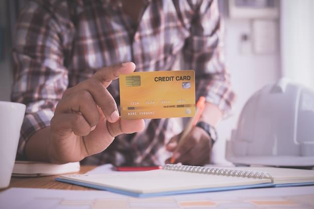 Empresário, mostrando uma simulação de cartão de crédito.