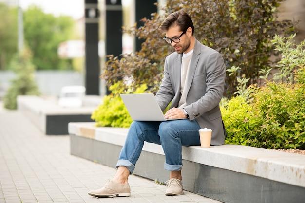 Empresário móvel ou freelancer de jaqueta e jeans, sentado em um ambiente urbano em frente ao laptop e trabalhando na rede