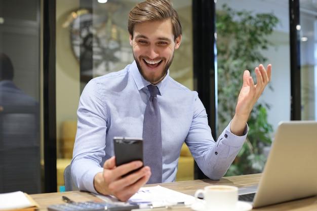 Empresário muito feliz lendo excelente mensagem em seu telefone celular no escritório.