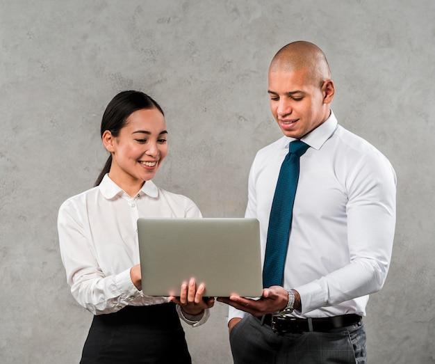 Empresário multiétnico e empresária olhando para laptop em pé contra a parede cinza