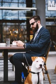 Empresário na cafeteria com o cachorro. melhores amigos no café.