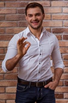 Empresário na camisa branca e calça jeans mostrando sinal de ok.