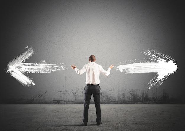 Empresário na frente de uma escolha com setas em direções opostas