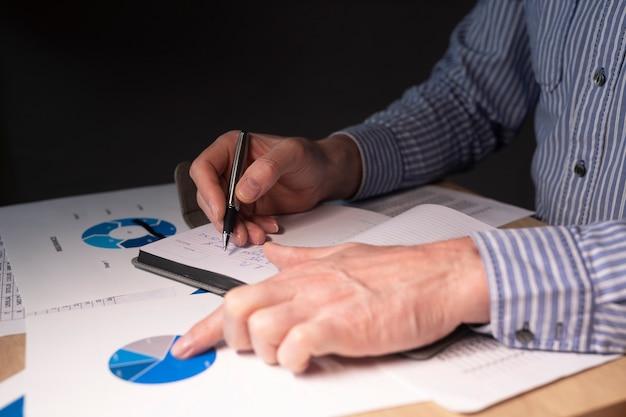 Empresário na mesa com documentos financeiros e caderno, preparando o relatório de finanças do negócio, análise contábil em gráficos.