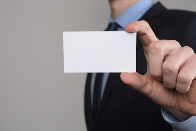 Empresário, negócios mans mão segura mostrando cartão de visita close-up tiro em cinza