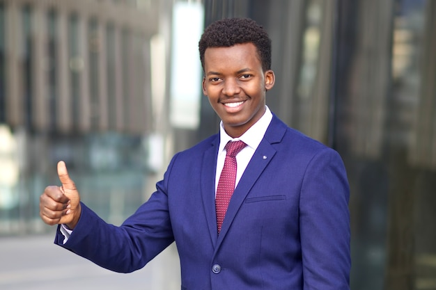 Empresário negro africano afro-americano de terno mostrando o polegar para cima e sorrindo