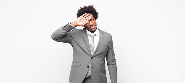 Empresário negro afro com aparência de estressado, cansado e frustrado, secando o suor da testa, sentindo-se desesperado e exausto