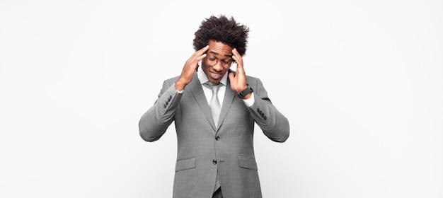 Empresário negro afro com cara de estressado e frustrado, trabalhando sob pressão, com dor de cabeça e preocupado com problemas