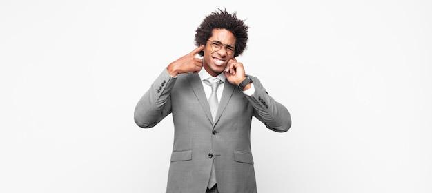 Empresário negro afro com cara de zangado, estressado e irritado, cobrindo os ouvidos para ouvir um barulho, som ou música alta ensurdecedores