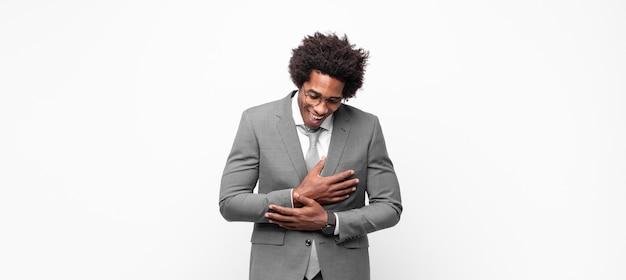 Empresário negro afro rindo alto de uma piada hilária, sentindo-se feliz e alegre, se divertindo