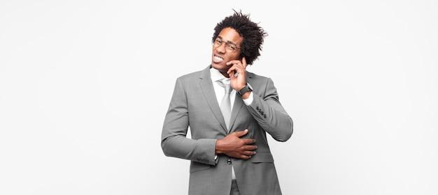 Empresário negro afro se sentindo estressado, frustrado e cansado, esfregando o pescoço dolorido, com um olhar preocupado e perturbado