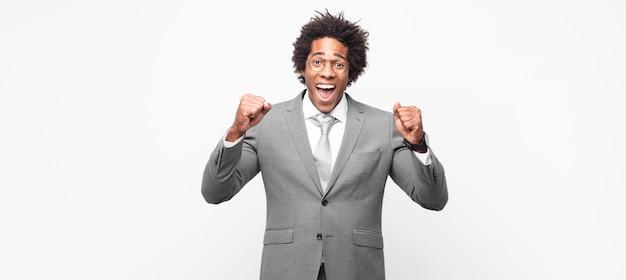 Empresário negro afro se sentindo feliz, positivo e bem-sucedido, comemorando vitória, conquistas ou boa sorte