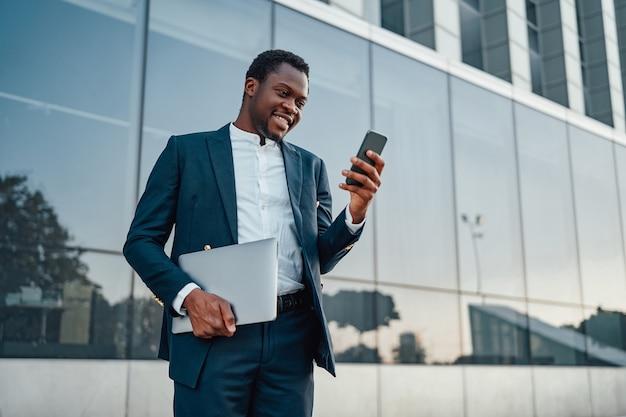 Empresário negro alegre com laptop e telefone inteligente