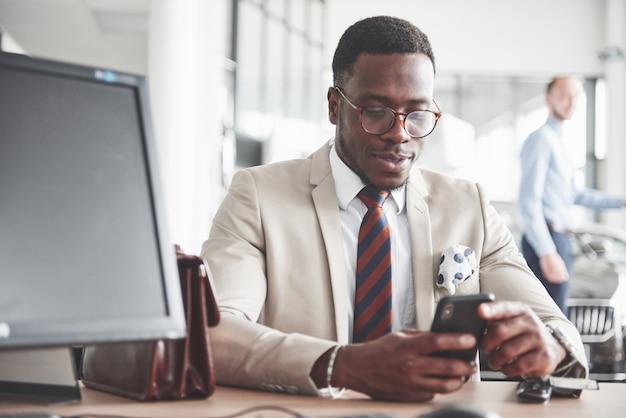 Empresário negro atraente se senta à mesa da concessionária, assina um contrato e compra um carro novo.