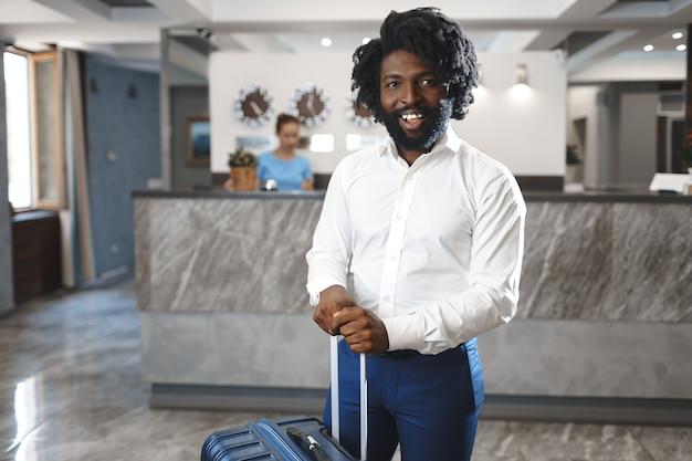 Empresário negro com bagagem arrumada parado no saguão do hotel