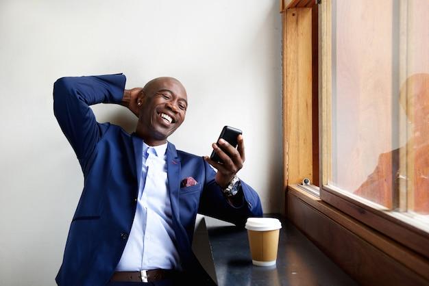 Empresário negro em um café usando o celular