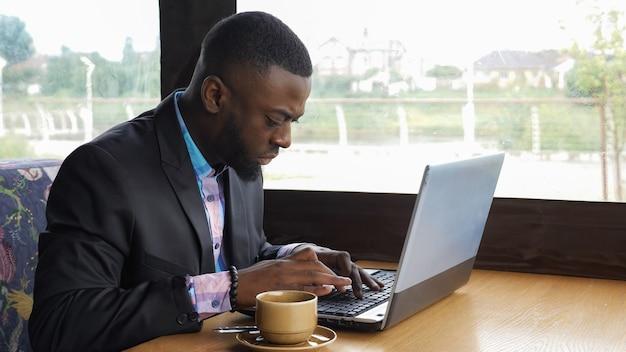 Empresário negro está trabalhando, digitando uma mensagem no laptop sentado no café de verão.