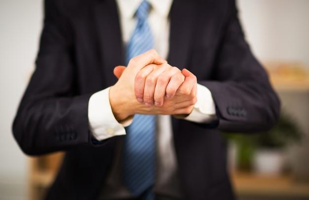 Empresário no escritório com as mãos postas. vontade de amizade e cooperação.