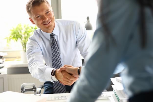 Empresário no escritório cumprimenta e aperta a mão com seu colega. conceito de arranjo de negócios