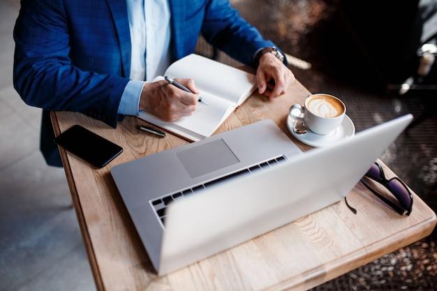 Empresário no escritório faz anotações em um caderno. um aluno trabalha em um laptop atrás de um laptop.