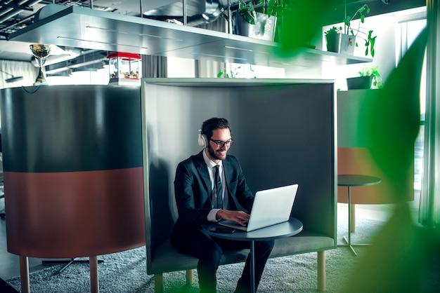 Empresário no escritório trabalhando no laptop, gerente de vendas online com fones de ouvido.