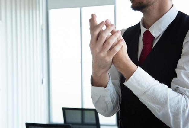 Empresário no escritório usando gel de álcool e esfregar as mãos