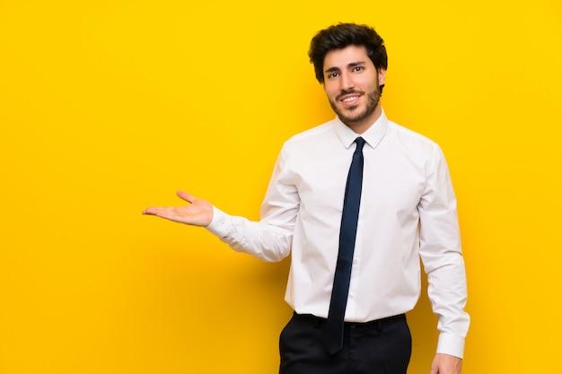 Empresário no isolado amarelo segurando copyspace imaginário na palma da mão