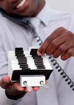 Empresário no telefone e olhando para um detentor de índice