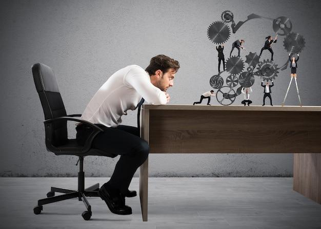 Empresário observa um trabalho em equipe de empresários trabalhando juntos em um sistema de engrenagens