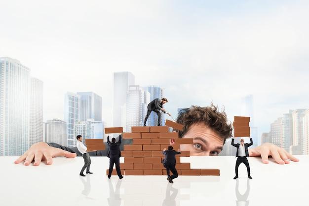 Empresário observa um trabalho em equipe de empresários trabalhando juntos na construção de uma parede de tijolos