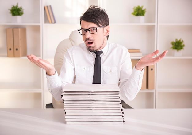 Empresário ocupado de óculos com um monte de pastas